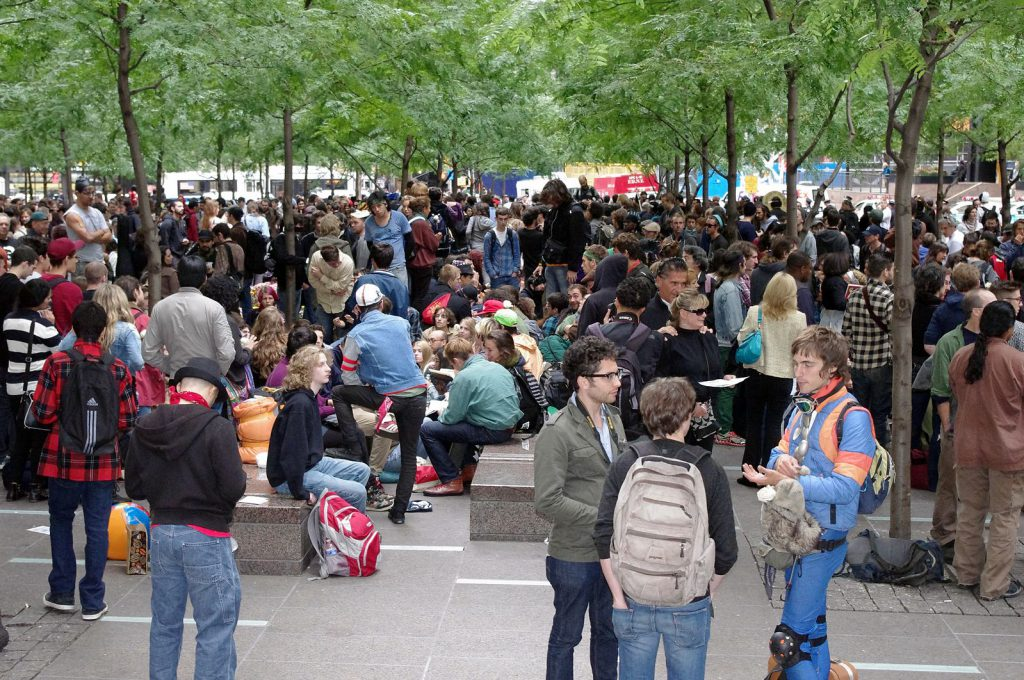 People gather in a square, many in conversation in small groups.