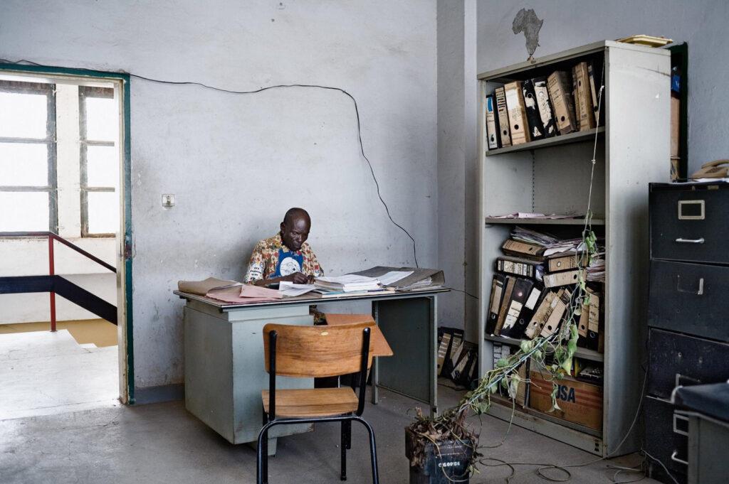 A man writing at an office desk.